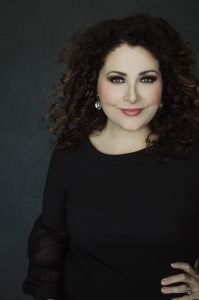 White woman curly hair portrait and headshot photographer standing confidently arm on hip wearing black top and earrings
