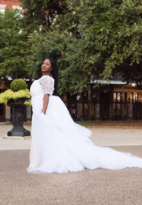 Beautiful smiling black African-American woman with braids standing in park outdoors wearing white lace wedding dress