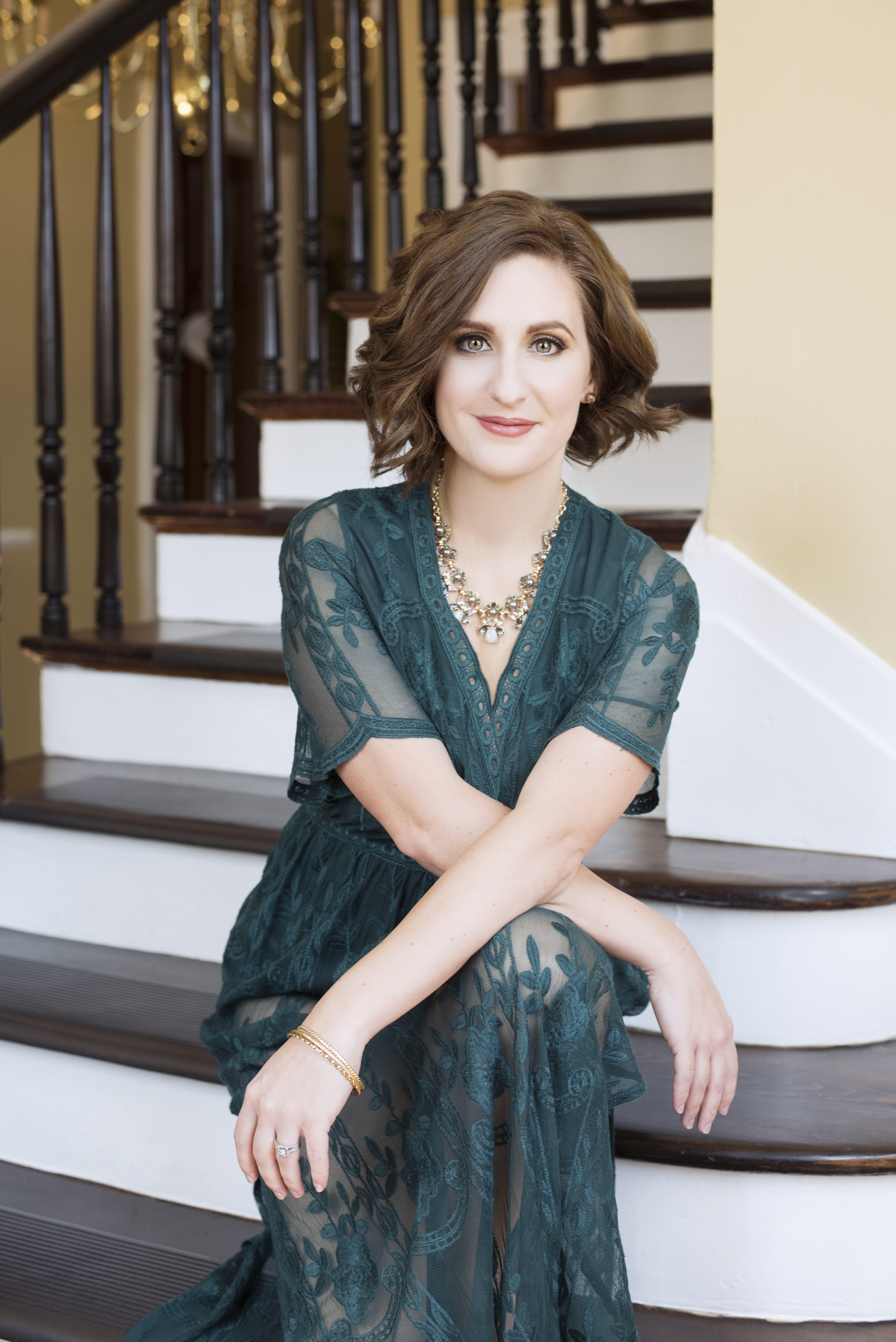 Beautiful smiling white woman with short brown hair wearing a green lace dress arms crossed sitting on staircase