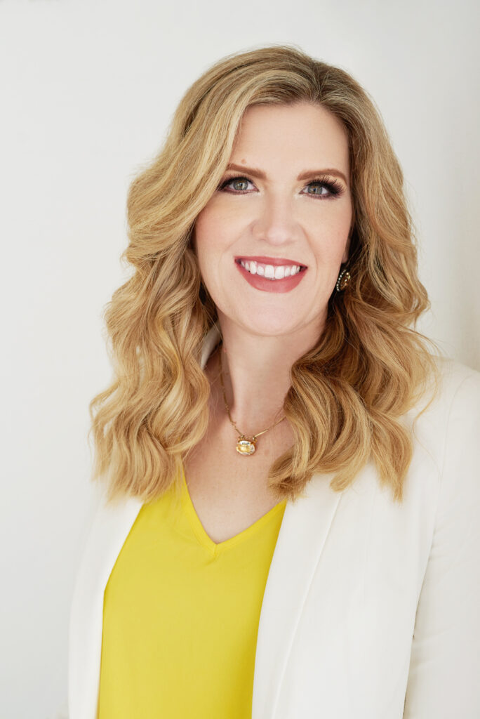 Headshot of a smiling white woman with medium wavy blonde hair wearing a yellow shirt and white blazer