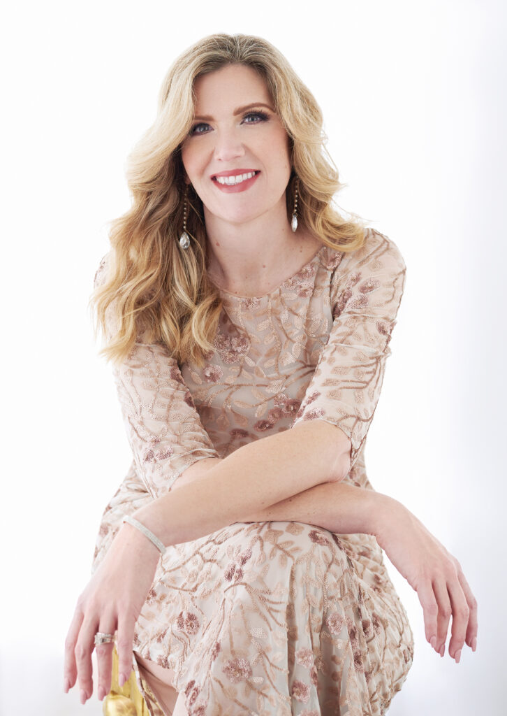Glamour shot of a smiling white woman with medium wavy blonde hair wearing a tan/beige lace dress with her arms crossed