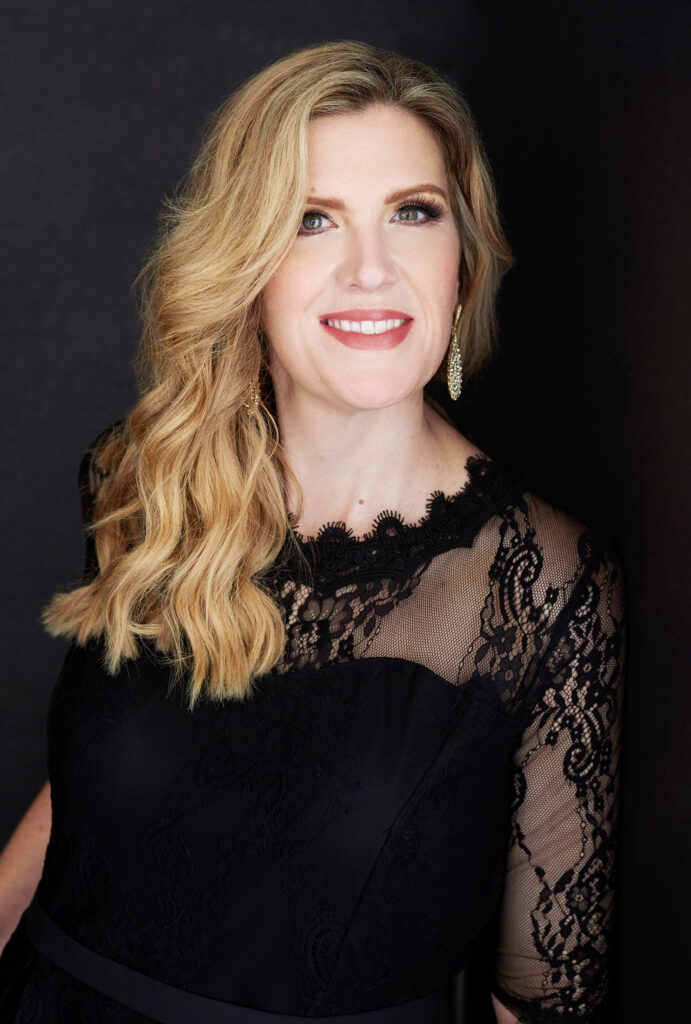 Beautiful smiling white woman with medium wavy blonde hair wearing a black lace top