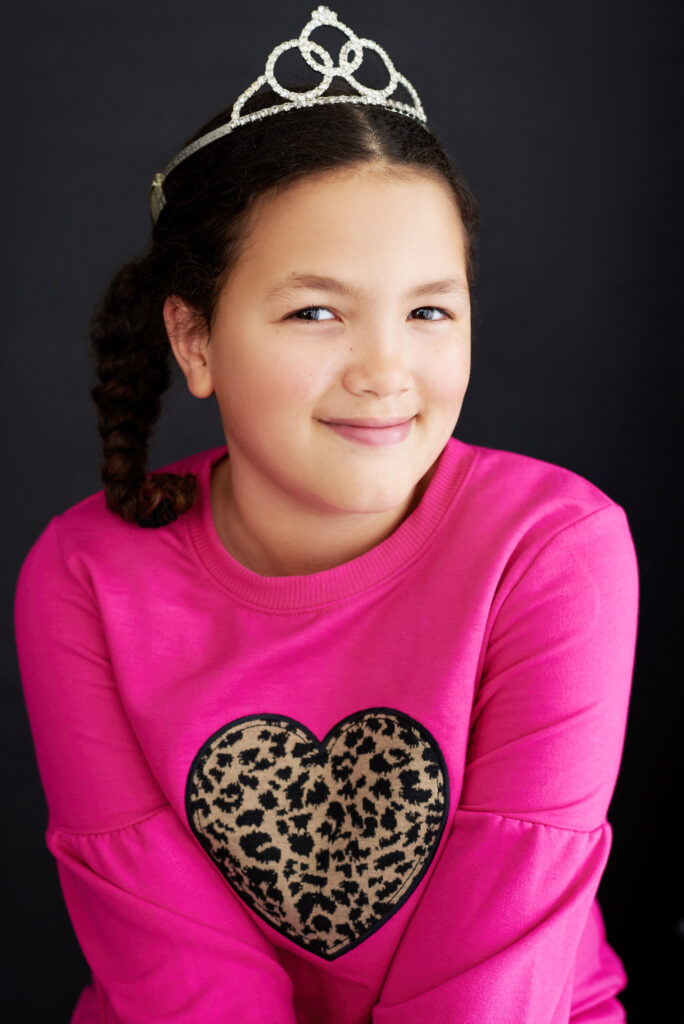 Glamour shot of sweet young girl with dark brown/black hair in a ponytail wearing a pink shirt and a princess crown