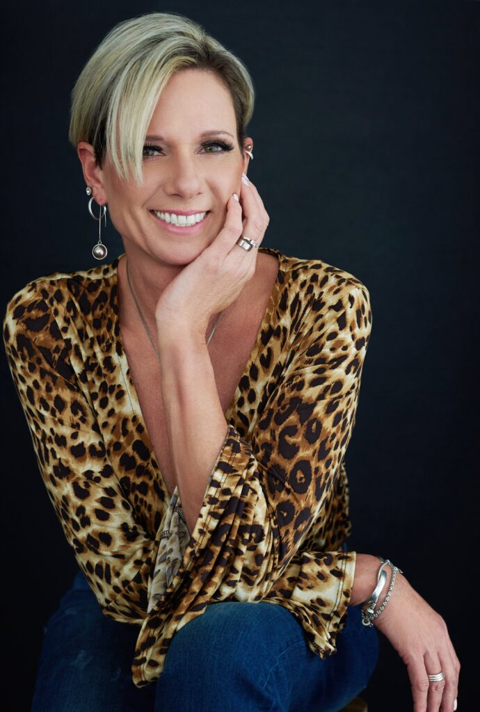 Beautiful smiling white woman with short blonde hair wearing a leopard print top