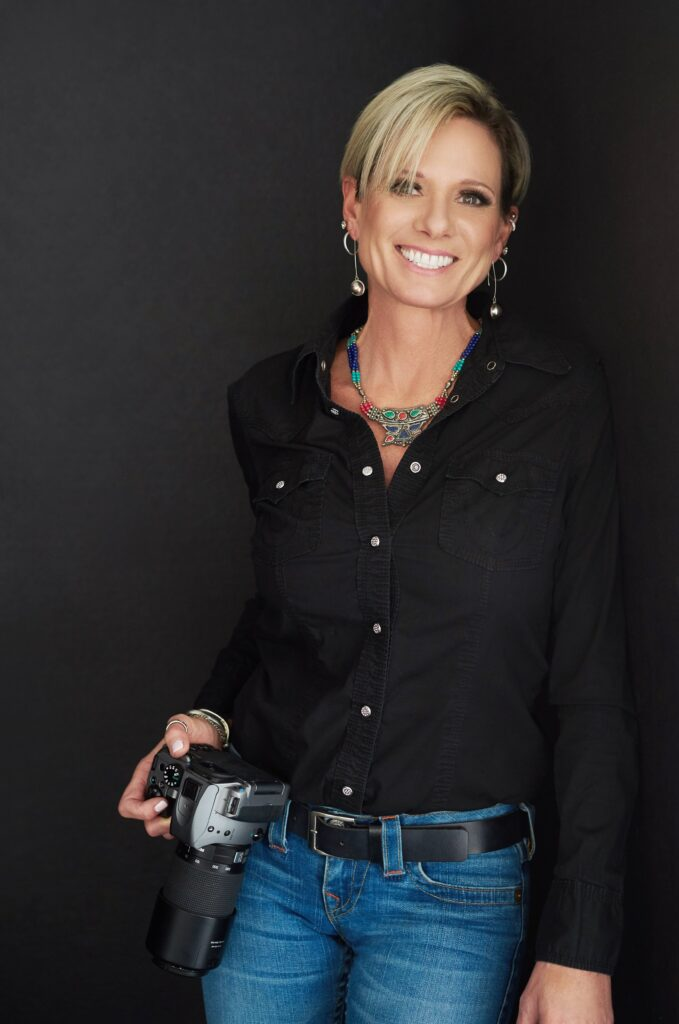 Beautiful smiling white woman photographer with short blonde hair wearing a black top, turquoise necklace, and holding a camera