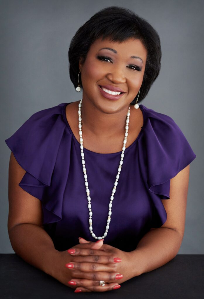 Beautiful smiling black African American woman with short black hair wearing a purple blouse/top/shirt and a long necklace with earrings. Professional headshot and glamour shot.