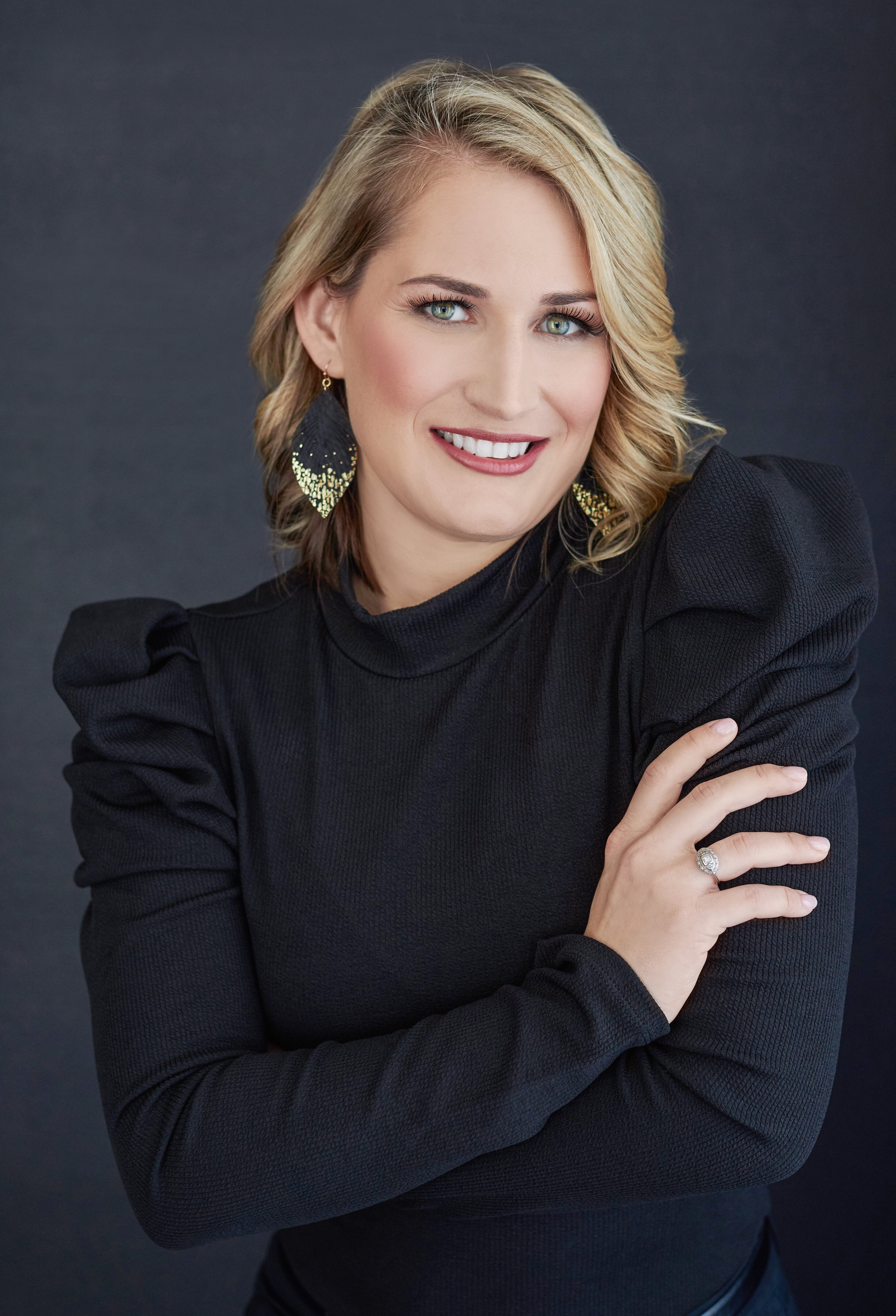 Beautiful smiling white woman with short blonde hair wearing a black dress. Professional headshot and glamour shot.