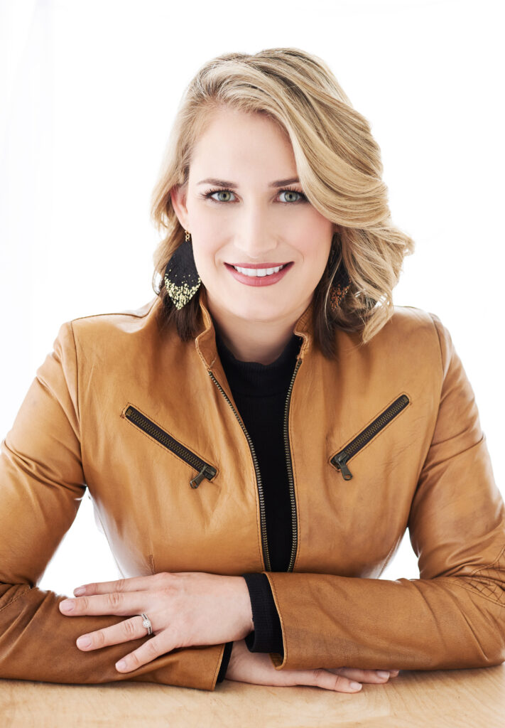 Beautiful smiling white woman with short blonde hair wearing a tan jacket. Professional headshot and glamour shot.