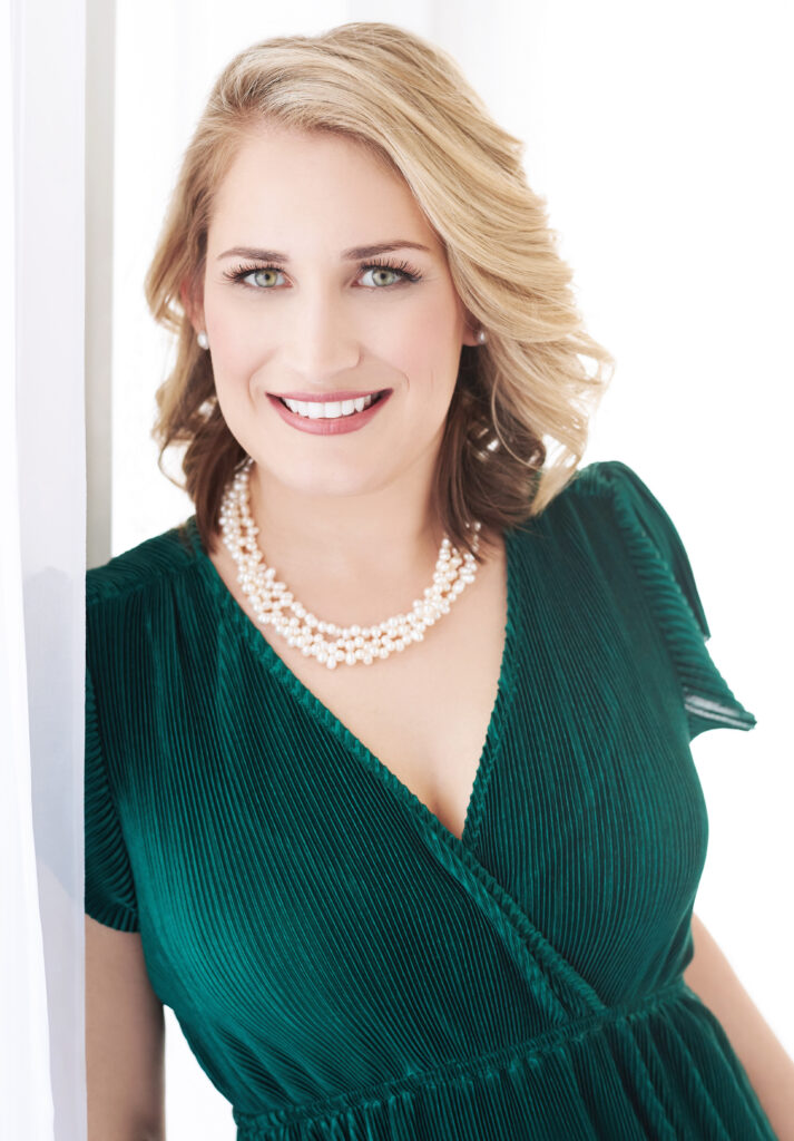 Beautiful smiling white woman with short blonde hair wearing a green dress and pearl necklace. Professional headshot and glamour shot.