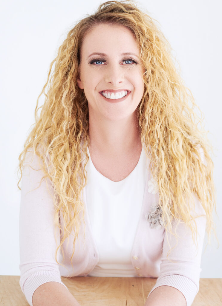 Beautiful smiling white woman with long blonde hair wearing a white blouse. Professional headshot and glamour shot.