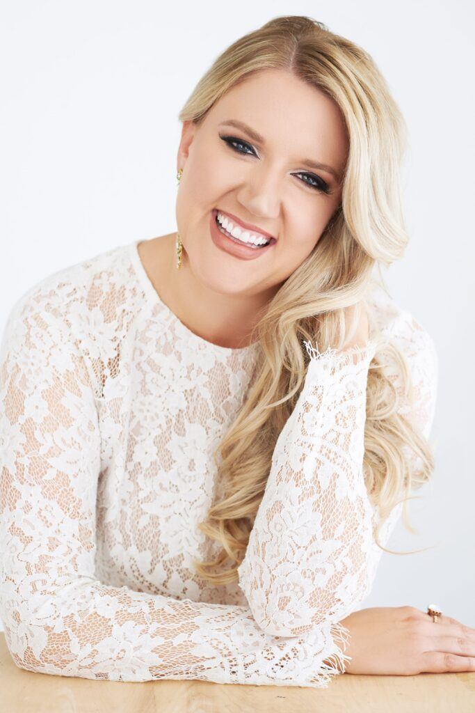 Beautiful smiling white woman with long blonde hair wearing a white lace blouse. Professional headshot and glamour shot.
