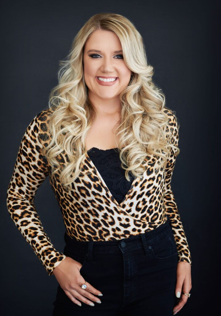Beautiful smiling white woman with long blonde hair wearing a leopard print blouse. Professional headshot and glamour shot.