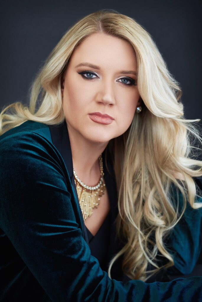Beautiful smiling white woman with long blonde hair wearing a teal blouse. Professional headshot and glamour shot.