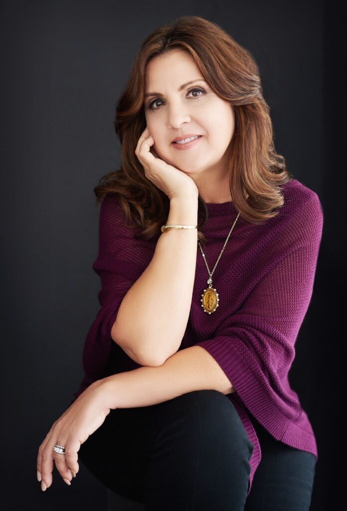 Beautiful smiling white woman with short brunette hair wearing a purple sweater and black pants. Professional headshot and glamour shot.