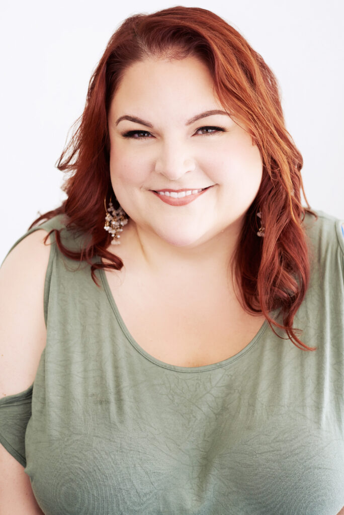 Beautiful smiling white woman with red hair wearing a green t-shirt.