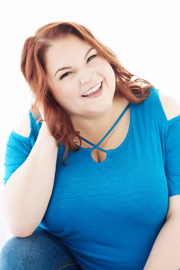 Beautiful laughing/smiling white woman with red hair wearing a blue t-shirt.