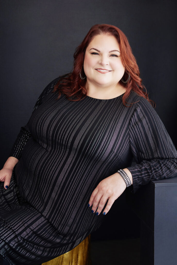 Beautiful laughing/smiling white woman with red hair wearing a black striped dress