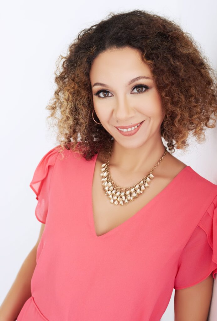 Beautiful smiling woman with curly brown hair wearing a pink blouse. Professional headshot and glamour shot.