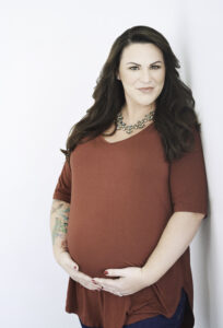 Beautiful pregnant smiling brunette woman with tattoos wearing a red shirt