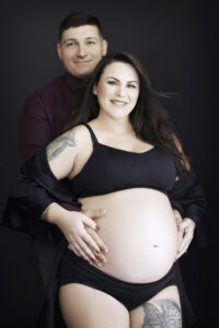 Smiling pregnant brunette woman with husband, maternity shoot