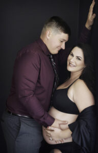 Smiling brunette woman with husband, maternity shoot